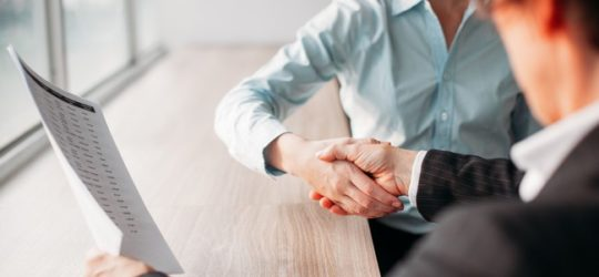 Unrecognizable businesswoman holding document and shaking hand of business partner after signing of contract. They sitting at table. Negotiation concept